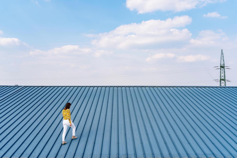 Unternehmensdach: Eine Frau will nach oben.