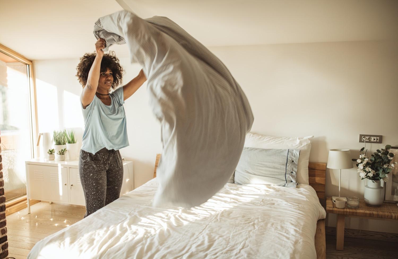 Kleiner Griff mit großer Wirkung: Ein gemachtes Bett lässt das Schlafzimmer gleich viel ruhiger wirken.
