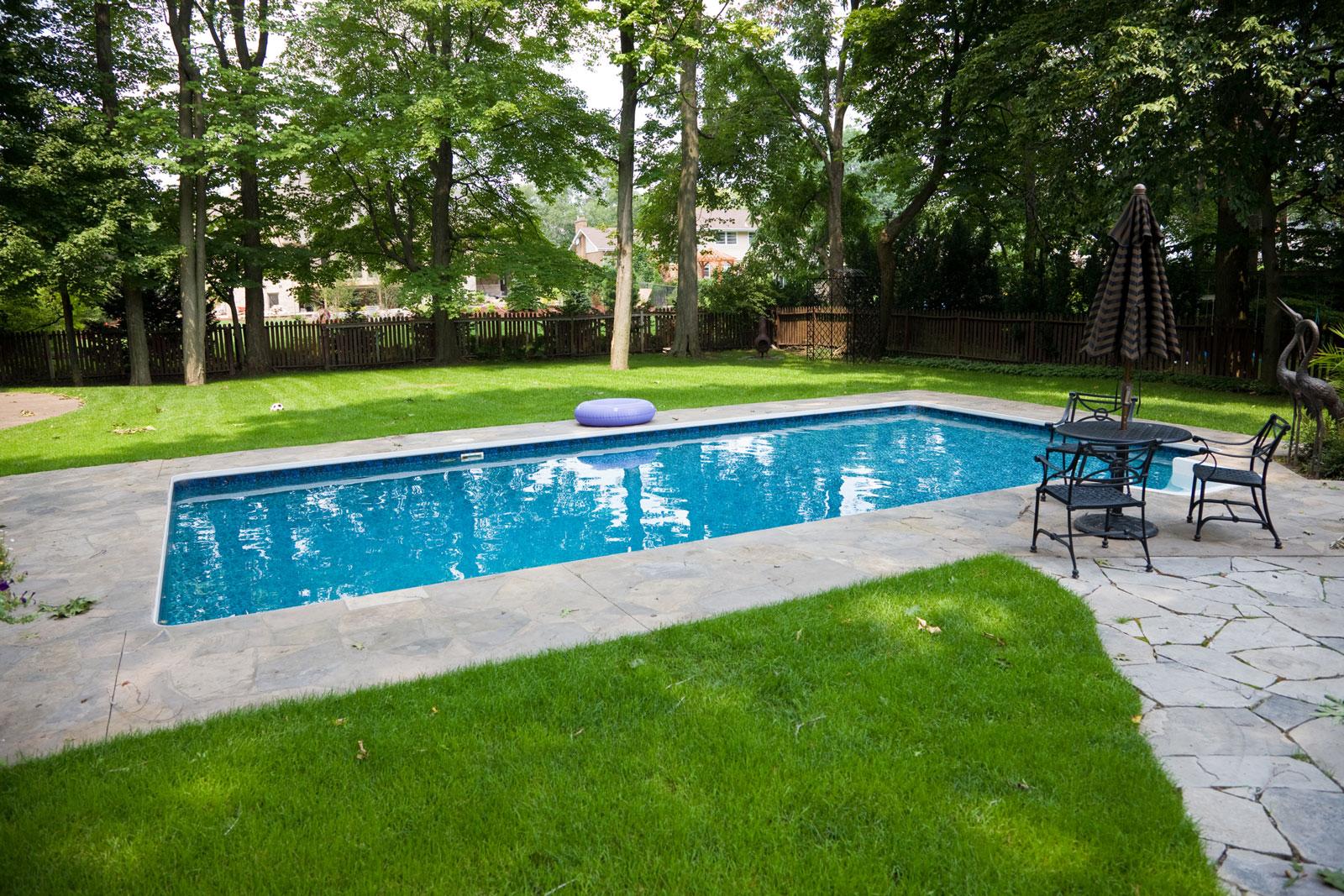 Schutzrand: Mit Steinen und Holz um den Pool bleibt das Wasser länger sauber.