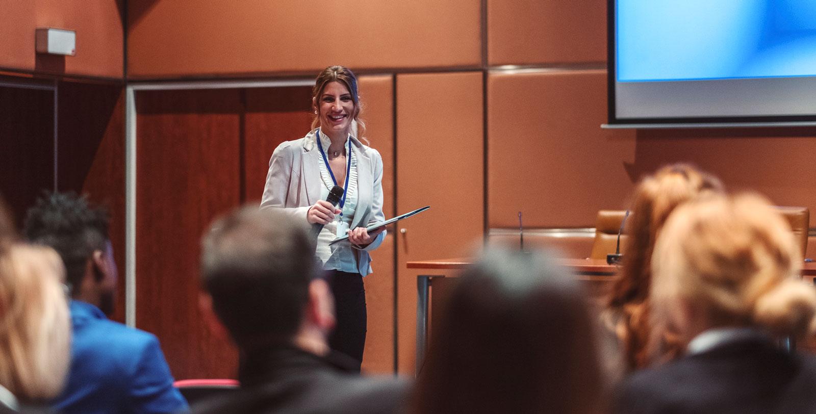 So gewinnst du dein Publikum: Lächle deine Zuhörer an und unterstreiche deinen Vortrag mit Gesten.
