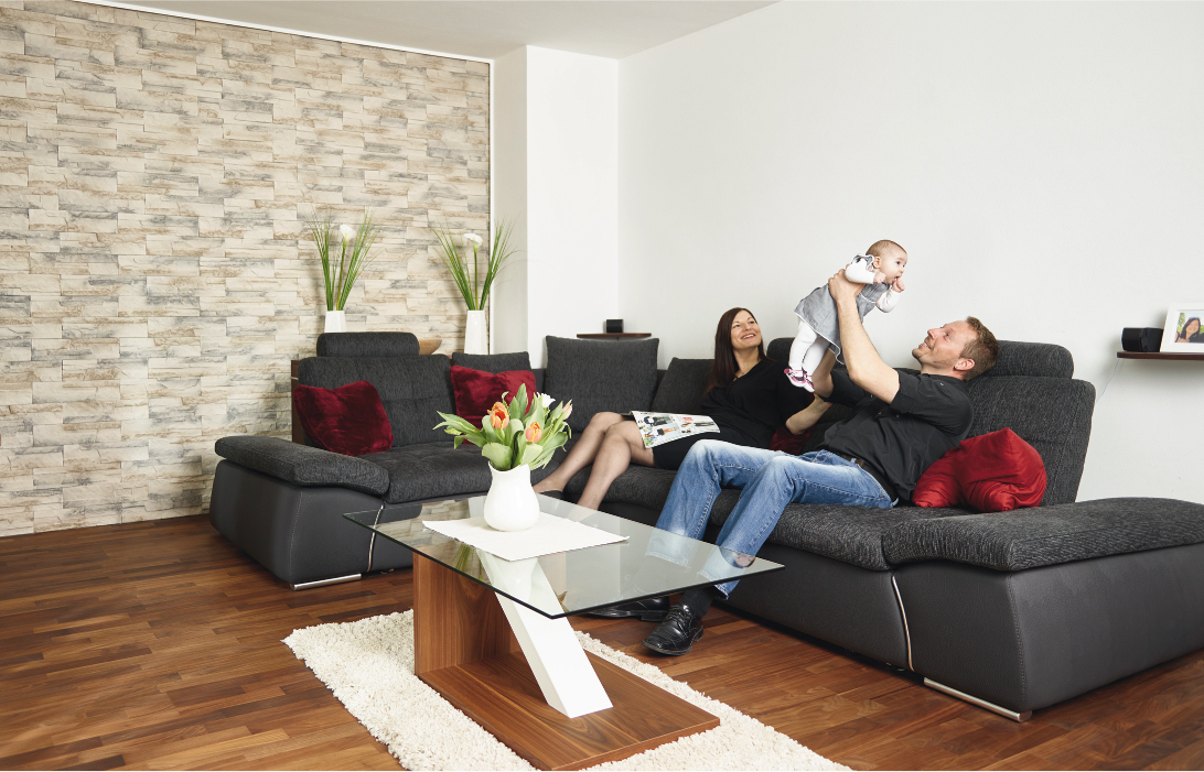 Gemütliche Fernsehecke mit Sofa: Der Holzboden und die Steinwand sorgen für eine besonders warme Stimmung.